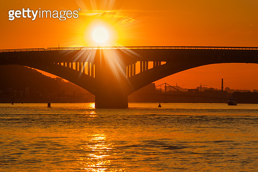 Silhouette of bridge across river and setting sun over it