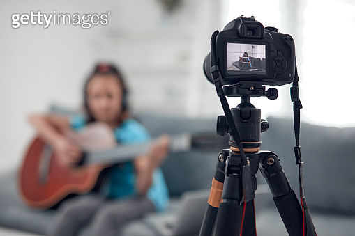 Child guitarist making video lessons and tutorials for internet vlog website classes.