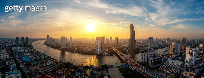 Panorama of Bangkok business district skyline and office skyscraper with Chao Phraya River during sunset in Bangkok, Thailand. Thailand tourism, modern city life, or business finance and economy concept.