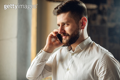 Caucasian adult bearded man indoors in cafe. Lifestyle concept photo with copy space. Picture with serious guy who calling on phone