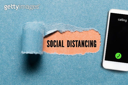 torn paper revealing message SOCIAL DISTANCING beside a smartphone on paper background