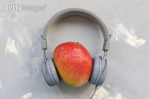 Mango and headphones on gray background