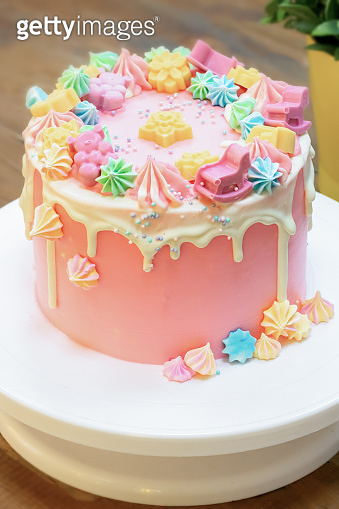 Party cake covered by pink and white cream with colorful meringue, chocolate bears, flowers and stars, and tiny confetti.