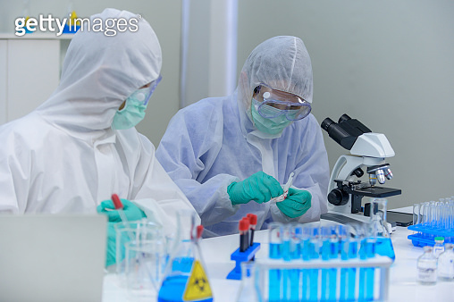 Scientist team researching Coronavirus cure in the laboratory. Asian Doctor working on vaccine against virus infection.