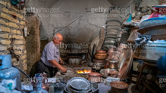 Iranian man working with copper cookware in his copper store, Yazd, Iran
