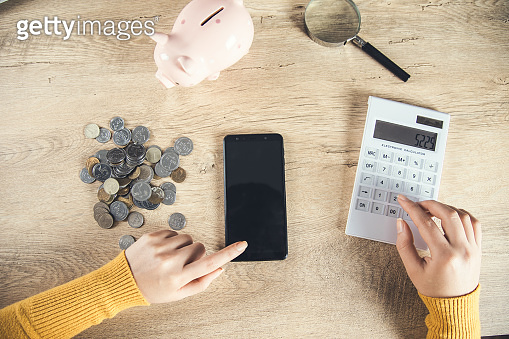 woman hand phone with coins and calculator