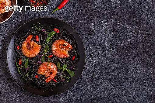 Italian pasta black spaghetti with shrimp and microgreens