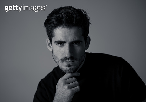 Portrait of young handsome manly man looking sexy and sensual with beautiful dark ayes and hair. Studio shot of spanish masculine model posing . In fashion, natural beauty, modeling and lifestyle.