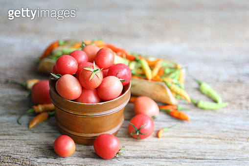 Tomato in rustic basket on wooden table