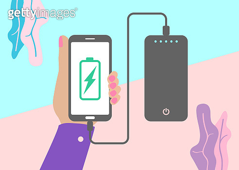 flat lay modern minimal hand holding mobile phone charging from portable battery or powerbank
