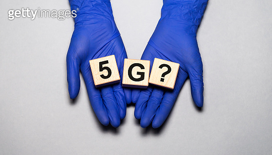 5G ? inscription on wooden cubes in hands in medical gloves on grey background