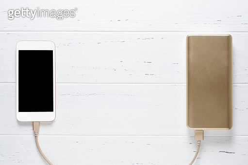 Portable power Bank and smartphone on white wooden background. Copy space