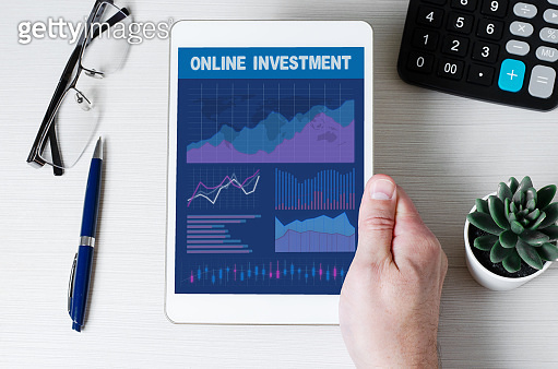Online investment. Tablet with graphs and diagrams in men's hands