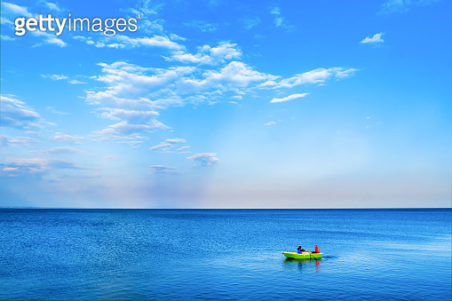 A green boat is sailing in the blue sea against the background of cloudy clouds.