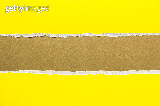 Yellow ripped pieces of cardboard on golden brown paper texture background. Copy space for text message.