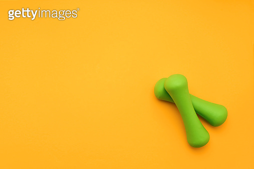 Green dumbbells lie on orange background. The concept of healthy lifestyle. Copy space, top view