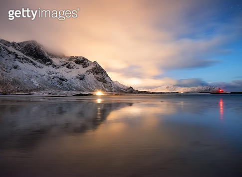 Mountains and reflections on beach at night. Winter landscape. The sky with stars and clouds in motion. Nature as a background. Norway - travel