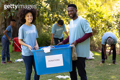 Multi-generation people collecting garbage with a couple holding a box written Donation