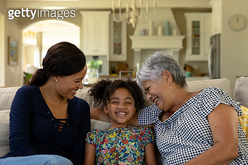 Mixed race woman sitting on the couch with her senior mother and her young daughter