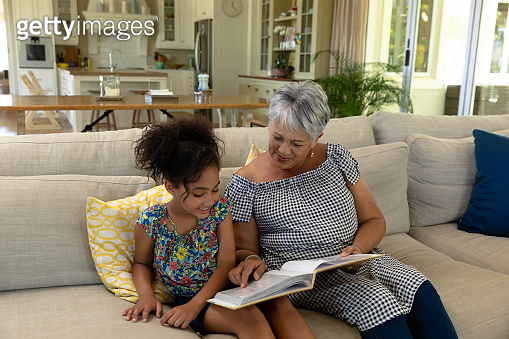 Senior mixed race woman reading with her granddaughter