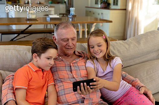 Grandfather and grandchildren at home in the living room