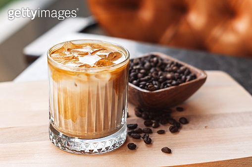 Iced latte coffee with milk and ice cubes served on wood
