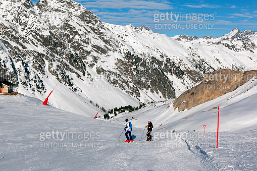 Two skiers chattering cheerfully on a ski slope and preparing to ski down