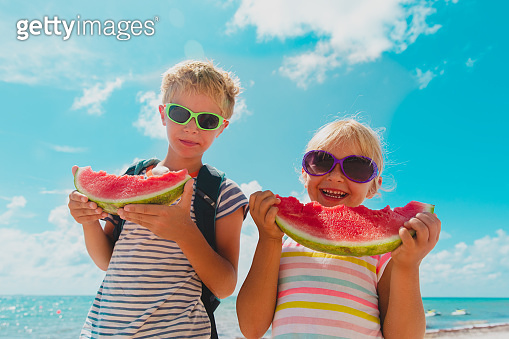 happy boy and girl eat watermelon at beach, healthy lifestyle