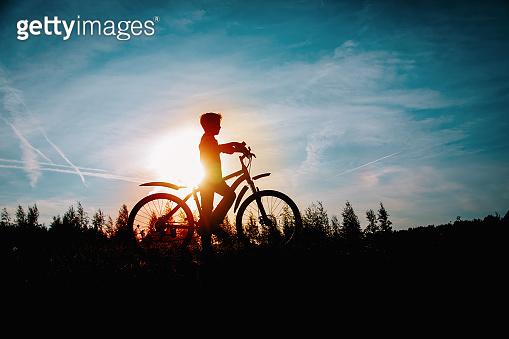 happy kid riding bike at sunset nature