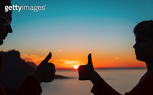 happy father and son thumb up at sunset, family enjoy hiking in nature