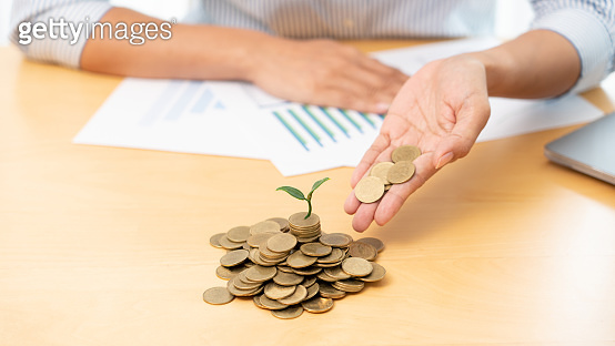 Hands of businessman putting coin into plant sprouting growing up to profit, demonstrating financial growth through saving plans and investment schemes