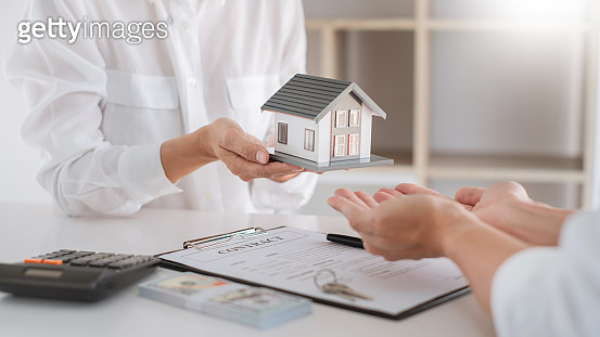 Real Estate concept, Agent with calculator for present price for loan house for investment documents and calculating table payment to customer
