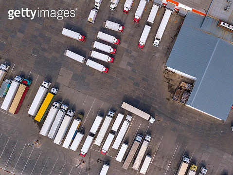 Aerial shot of trucks on warehouse parking terminal.
