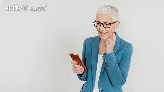 Isolated Shot of Stylish Senior Woman using Smartphone