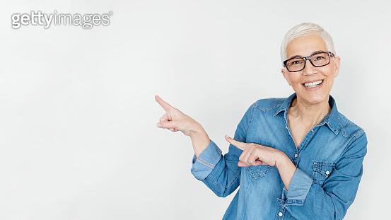 Senior Woman Pointing Away