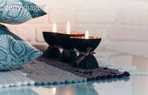 Burning spa aroma candle in coconut shell on a knitted multicolored rug and gray pillows opposite the white wall, cozy home interior