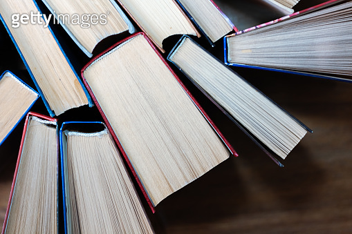 Old and well used hardback books or text books in a book shop or library. Many Books Piles. Hardback books on wooden table top view. Back to school background with copy space