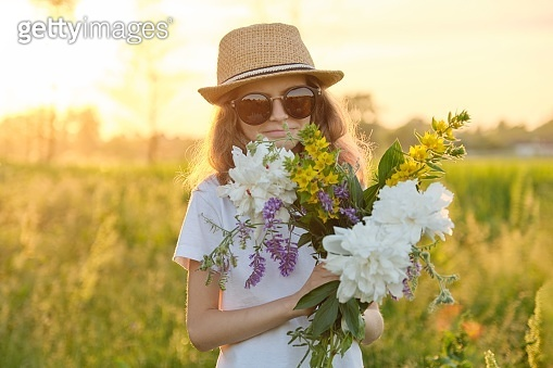 Portrait of child girl in hat sunglasses with flowers in meadow