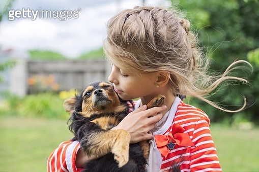 Girl child hugging dog outdoor, friendship and love between small owner and pet.