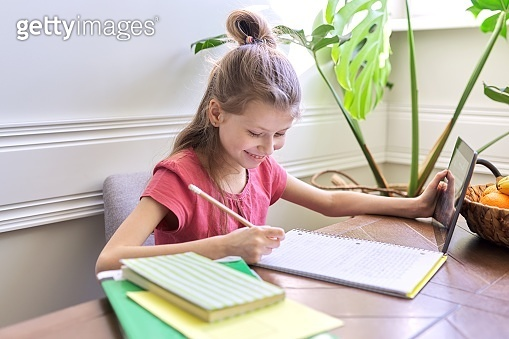 Girl child studying at home using digital tablet