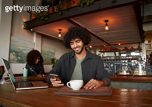 Handsome young man using smartphone and laptop in modern cafe while drinking coffee