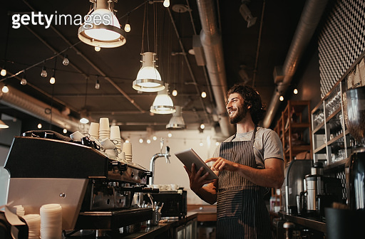 Smiling caucasian man wearing apron standing behind cafe counter using digital tablet looking away