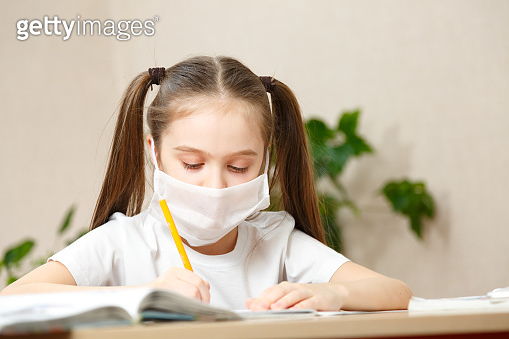 Distance learning online education. schoolgirl in medical mask studying at home,