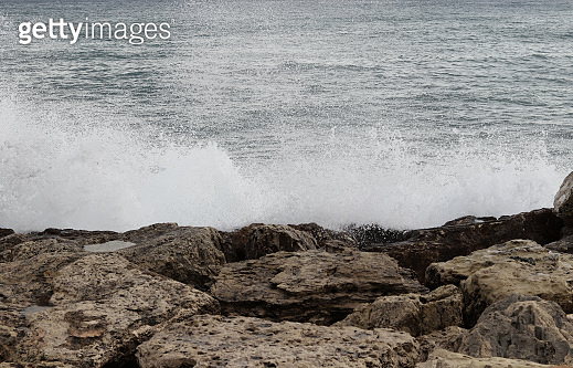 Huge masses of salt water converge and crash into the cliffs, creating dangerous eddies off the Paphos coast in western Cyprus. Sparkling sound lines across the coast. Foamy water