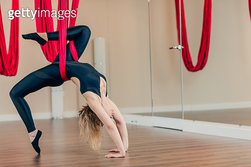 Young woman in black jumpsuit performs antigravity yoga exercise in yoga studio