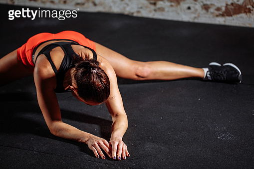 woman sport stretching in gym with brick wall and black mats
