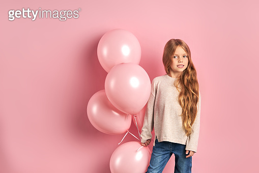Portrait of beautiful girl kid holding pink air balloons
