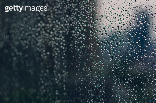 Blurred and focus of rain drop on glass window in monsoon season.