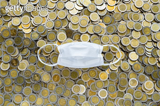 White face mask on background of Thai baht coins.