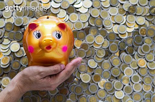 Hand holding piggy bank on blurred background of Thai baht coins.